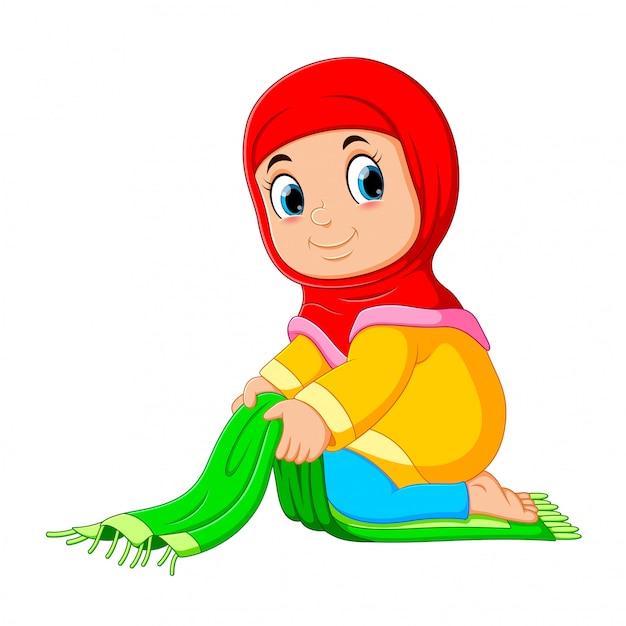 デリケートな女の子は彼女の緑の祈りの敷物を折っています Premiumベクター