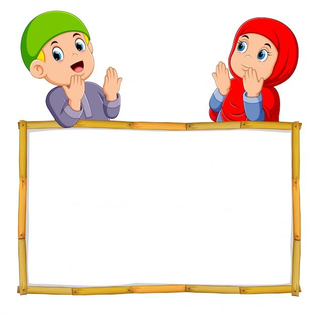 Двое детей молятся над деревянной рамой Premium векторы