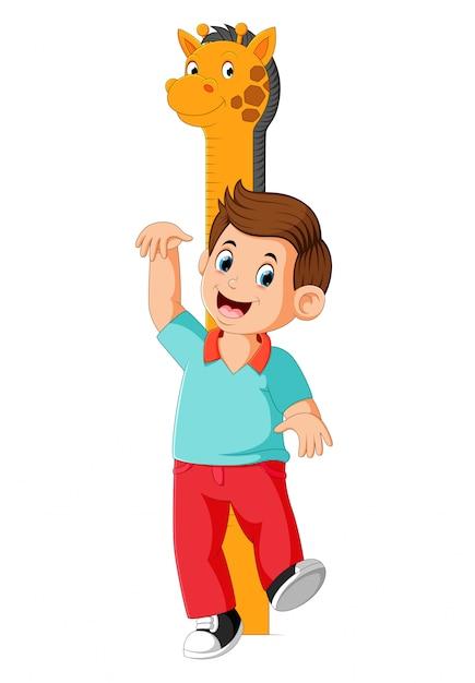 少年はキリンメジャーの高さに体で測定しています Premiumベクター