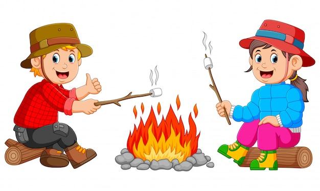 子供たちはキャンプでマシュマロを燃やしています Premiumベクター
