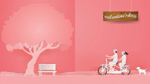 ピンクの背景の赤い芝生の上の自転車に乗るカップル Premiumベクター