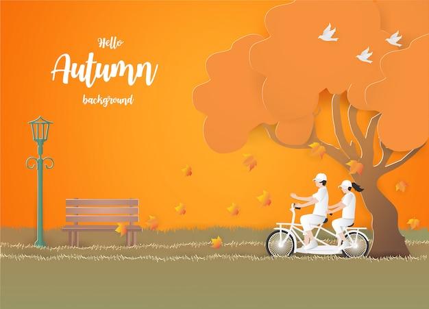 秋のバックグラウンドで草の上の自転車で旅行するカップル。 Premiumベクター