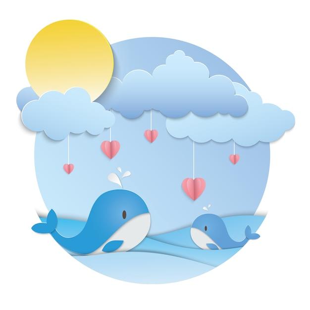Розовое сердце висит и два синих кита в океане Premium векторы