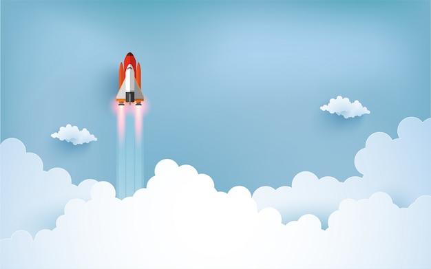 宇宙船のイラストが雲の上を飛んでいます。紙アートデザイン Premiumベクター