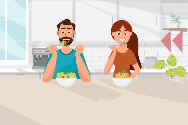 キッチンで食べ物、ベジタリアン、健康的なライフスタイルを食べるカップル Premiumベクター