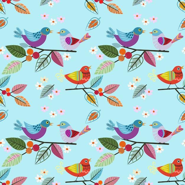 枝パターンに描かれた鳥を手します。 Premiumベクター