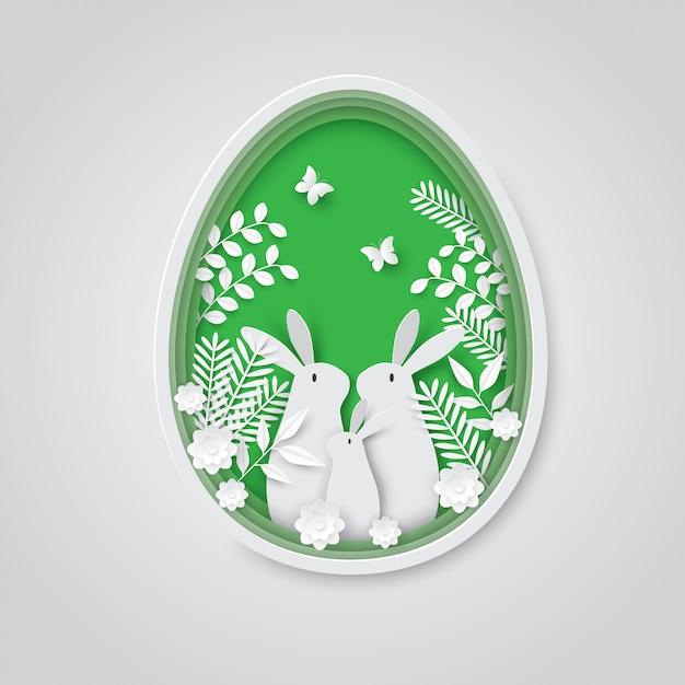 イースターホリデーペーパーカット背景、卵のウサギの家族。 Premiumベクター