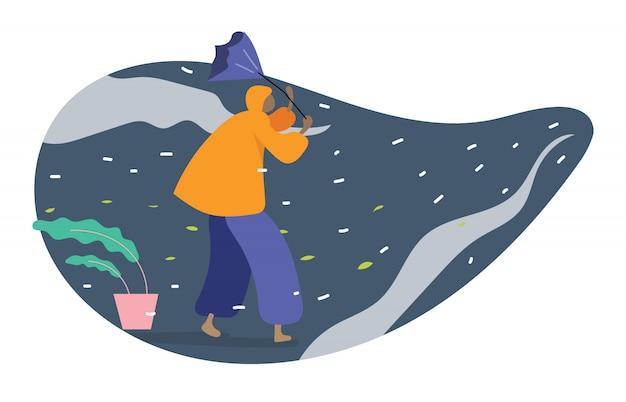 悪天候で傘を持って歩くレインコートを着た人間 Premiumベクター