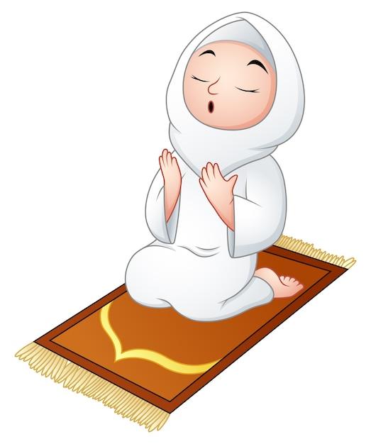 祈りながら祈りの敷物に座っているイスラム教徒の女の子 Premiumベクター