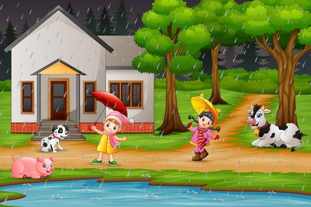 Мультяшный две девушки играют с животными под дождем Premium векторы