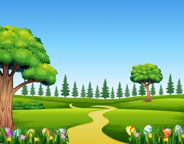 美しい風景と緑の芝生の上のカラフルなイースターエッグ Premiumベクター