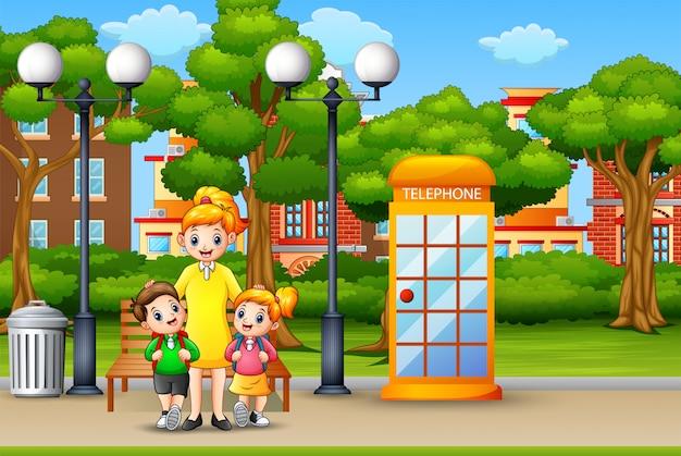 幸せな母親と子供たちは都市公園に立っています。 Premiumベクター