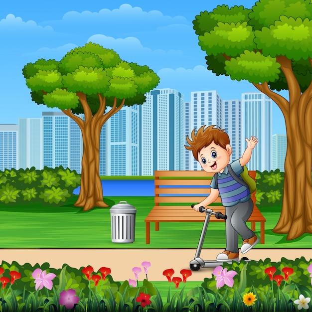 公園の街でスクーターに乗って小さな男の子 Premiumベクター