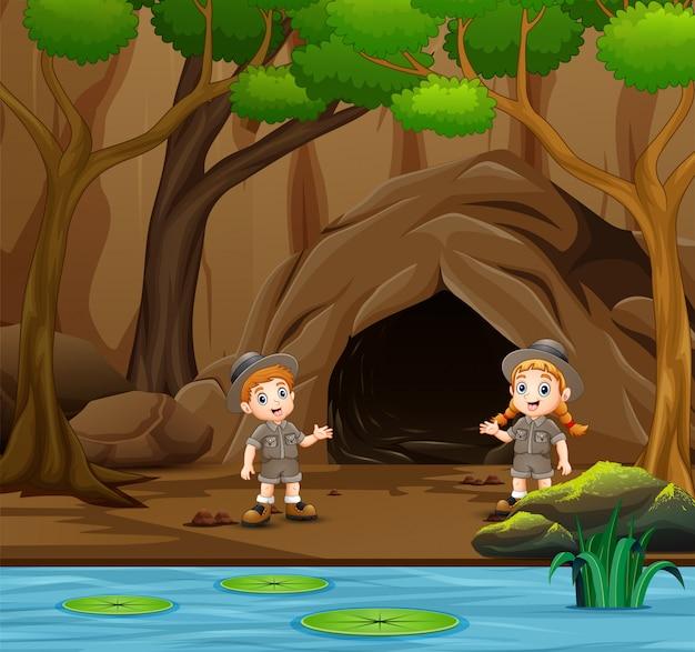 スカウトの男の子と女の子が洞窟の近くで話しています。 Premiumベクター