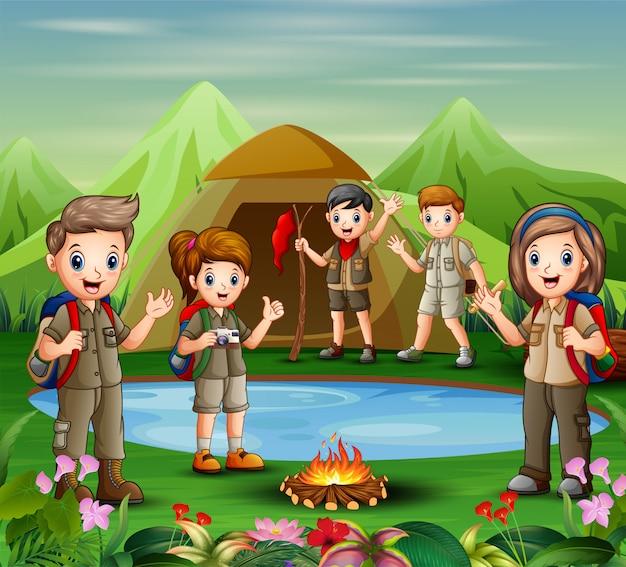 若いスカウトの女の子と男の子のグループは、自然の中で探索しています Premiumベクター