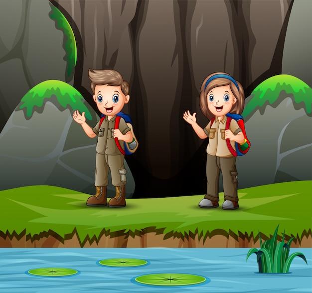 スカウトの少年と少女が自然を探索の漫画 Premiumベクター