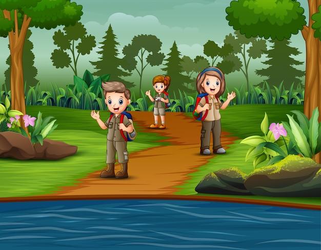 スカウトのグループが森を探索しています Premiumベクター
