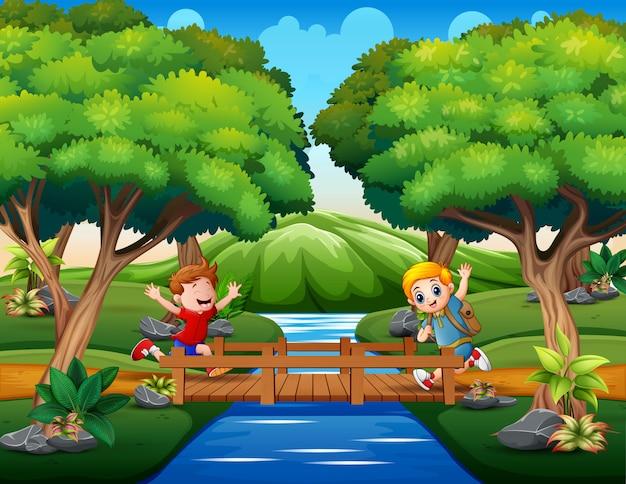 Счастливые мальчики бегали по деревянному мосту Premium векторы