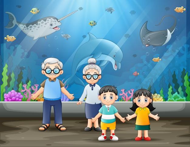 Пожилая пара и их внуки смотрят на рыб Premium векторы