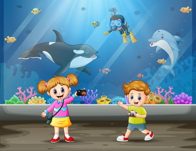 Дети фотографируют в аквариуме Premium векторы
