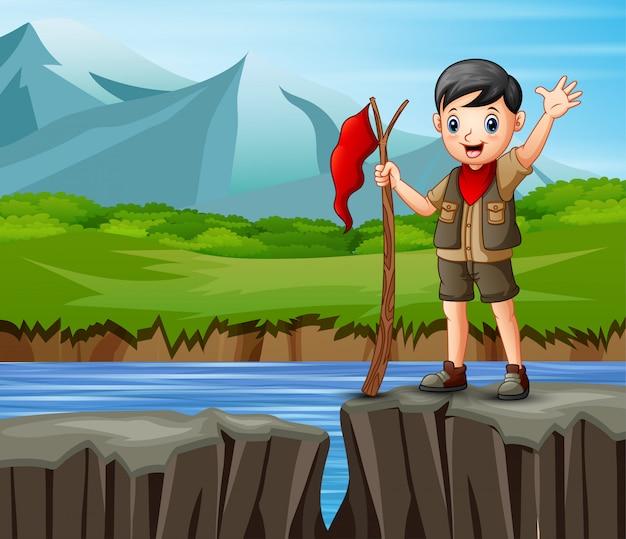 Скаутский мальчик стоит на краю обрыва с прекрасным видом Premium векторы