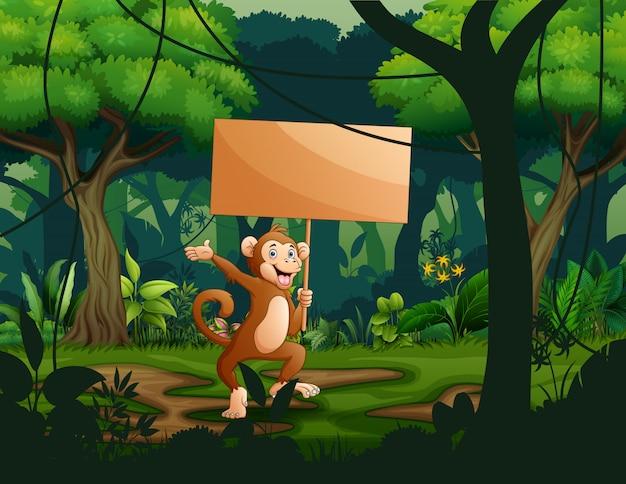 Обезьяна держит пустой деревянный указатель в лесу Premium векторы
