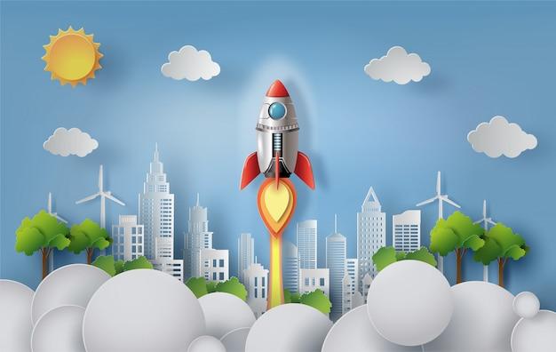 Бумажный стиль ракеты, летящей над современным городом Premium векторы