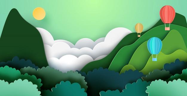 山と森の自然の風景の背景に熱気球。 Premiumベクター