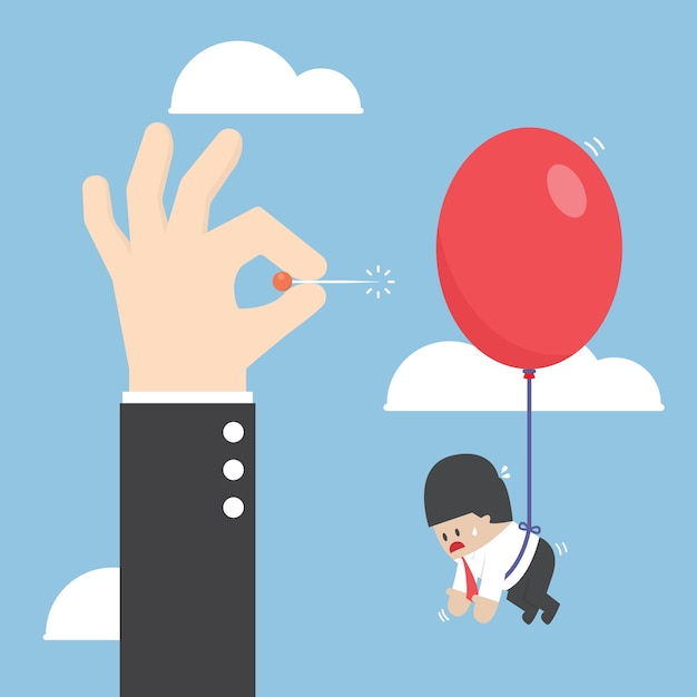 気球をポップするために針を押すビジネスマンの手 Premiumベクター