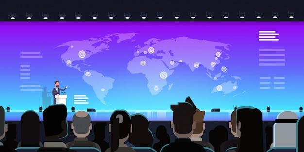 ビジネスマングループビジネスマンの前で世界地図上のビジネスプレゼンテーションをリードするビジネスマン Premiumベクター