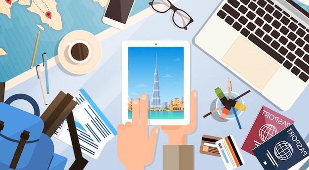 ドバイのスカイラインのパノラマ、パスポートが付いている旅行者の職場を持つ手持ち型タブレットコンピューター Premiumベクター
