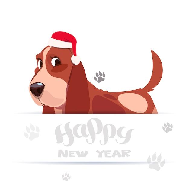 ハッピーニューイヤーグリーティングカードホリデーレタリングバナーにサンタの帽子でかわいいバセット犬 Premiumベクター