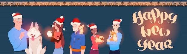 冬の休日かわいい犬とサンタの帽子をかぶっている人々のグループとの水平方向のバナー新年あけましておめでとうございます Premiumベクター
