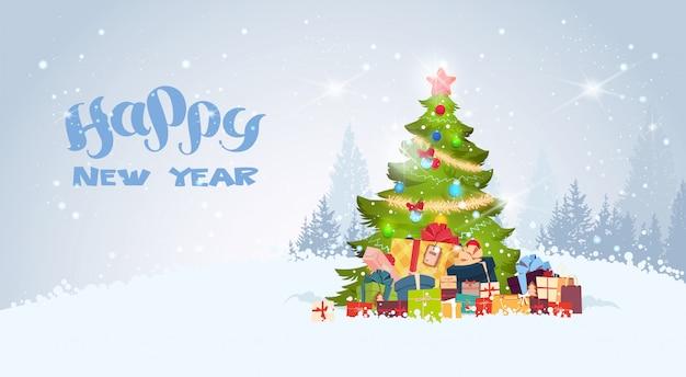 雪に覆われた冬の森の上に飾られたクリスマスツリーとハッピーニューイヤーの背景 Premiumベクター