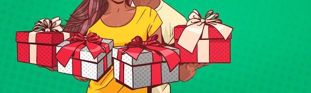 プレゼントボックスを保持している認識できないアフリカ系アメリカ人カップル水平バナーコミックピンアップれたら Premiumベクター