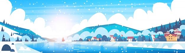 凍った川と山の丘のほとりの小さな村の家の冬の風景 Premiumベクター