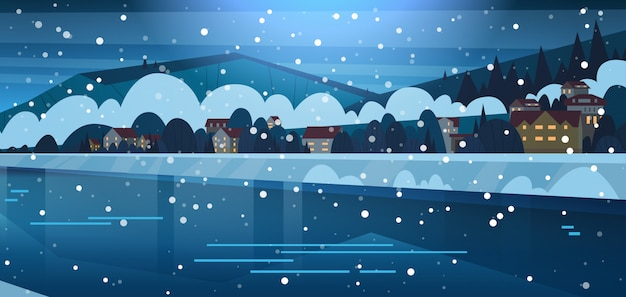覆われた凍った川と山の丘のほとりの小さな村の家の冬の風景 Premiumベクター