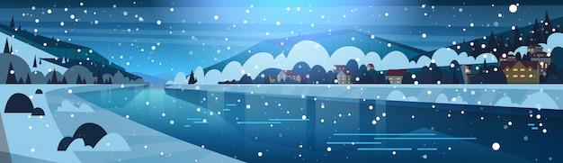 凍った川と山の丘のほとりの小さな村の夜の冬景色 Premiumベクター