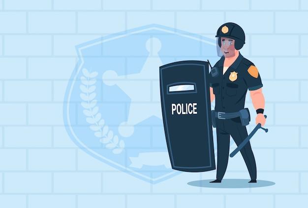 レンガの背景の上にヘルメット制服警官ガードを身に着けている警官ホールドシールド Premiumベクター