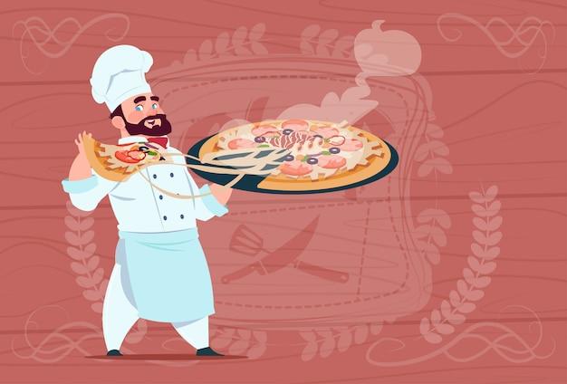 木製の織り目加工の背景の上の白いレストラン制服を着たピザ笑顔漫画チーフを保持しているシェフ料理 Premiumベクター