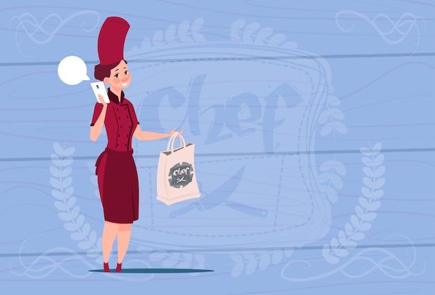 木製の織り目加工の背景の上にフードレストラン配達コンセプト漫画チーフが付いている女性シェフクックホールディングバッグ Premiumベクター