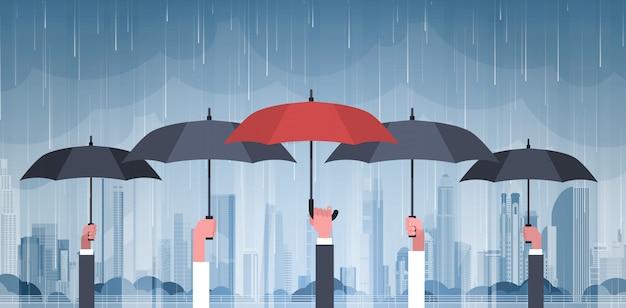 都市の嵐の上の傘を保持している手のグループ巨大な雨の背景ハリケーン竜巻町で自然災害の概念 Premiumベクター