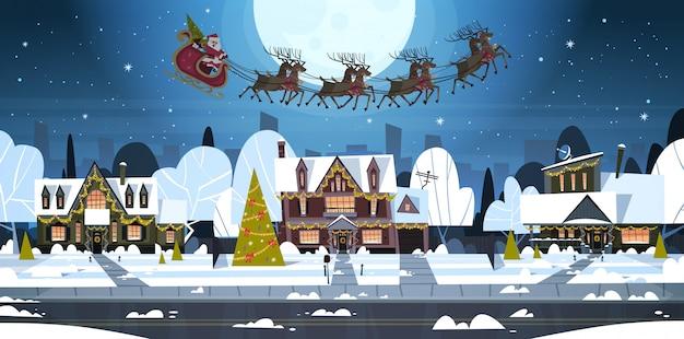 Санта летит в санях с оленями в небе над деревенскими домами, с рождеством и новым годом баннер зимние каникулы концепция Premium векторы