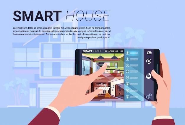 Рука держа цифровую таблетку с умным домашним интерфейсом, современной технологией концепции автоматизации дома Premium векторы
