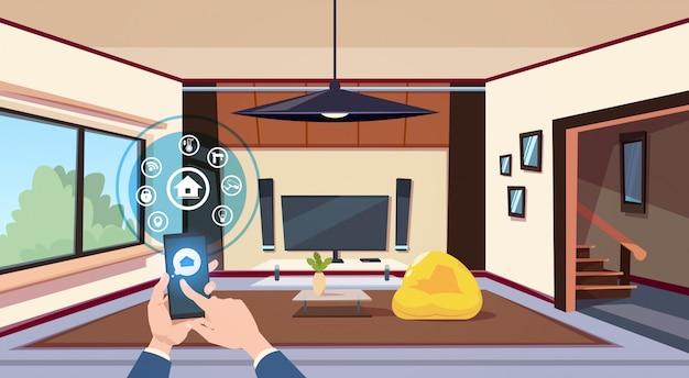 Рука, использующая приложение «умный дом» интерфейс панели управления над интерьером гостиной современная технология концепции мониторинга дома Premium векторы