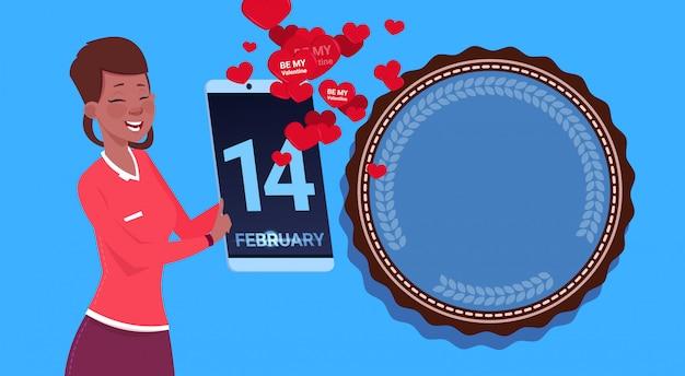 アフリカ系アメリカ人の女の子が青い背景上幸せなバレンタインデーおめでとうを送信するデジタルタブレットを保持します。 Premiumベクター