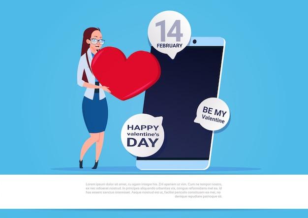 コピースペースで青い背景に幸せなバレンタインデーのお祝いを送る女性使用スマートフォン Premiumベクター