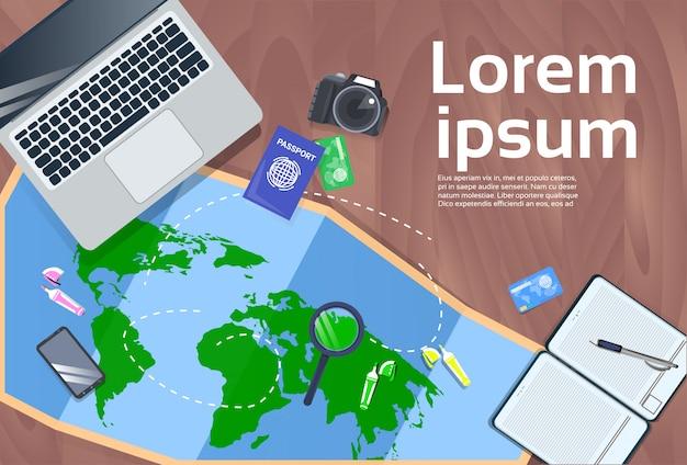 Планирование отпуска и концепция рабочего стола с ноутбуком, картой, фотоаппаратом и паспортом Premium векторы