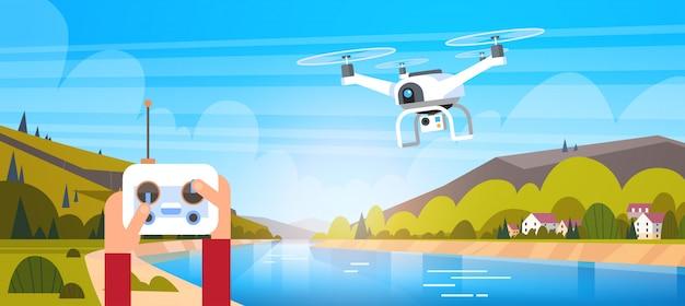 Руки держат пульт дистанционного управления для современного беспилотного летать над красивым натуральным Premium векторы