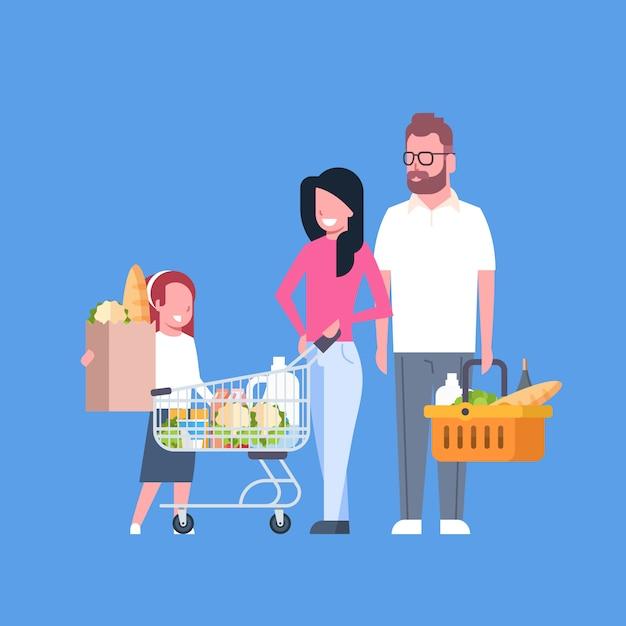 Молодая семья, делающая покупки, держащая бумажный пакет, тележку и корзину, полную продуктовых продуктов Premium векторы